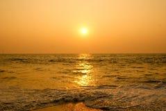 Zon die in een overzees strand plaatst. Stock Afbeelding