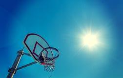 Zon die over een basketbalhoepel glanzen stock afbeeldingen