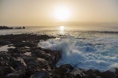 Zon die over golven plaatsen die op zeekust van het eiland van Tenerife breken Stock Foto's