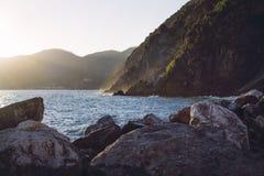 Zon die tegen de Ligurian bergen door de oceaan plaatsen, die tot gouden dampen van golven leiden die de rotsen raken stock foto