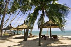 Zon loungeres en Paraplu's tegen blauwe overzees bij zon dag Mui Ne Stock Fotografie