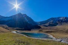 Zon over piek van Valbellahorn, meer van Altein, blauwe hemel stock afbeelding