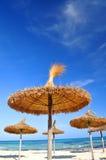 Zon parasols op een idyllisch strand Stock Afbeeldingen