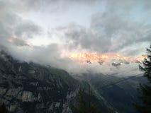 Zon` s bezinning over een rokerige berg stock foto