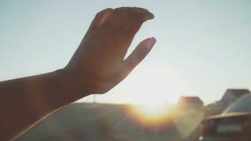 Zon` s stralen door vingers van vrouwelijke hand stock videobeelden