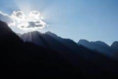 Zon in wolken tijdens zonsondergang in himalayan bergen stock afbeelding