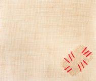 Zona con gli stitchs rossi sopra tela da imballaggio. Tela di sacco Fotografie Stock Libere da Diritti