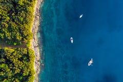 Zona costiera con tre barche su acqua blu Fotografia Stock