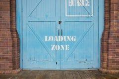 Zona de cargamento pintada en la puerta de madera azul foto de archivo