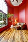 Zona de descanso con las paredes rojas, la ventana grande y el sofá del cuero Imagen de archivo libre de regalías