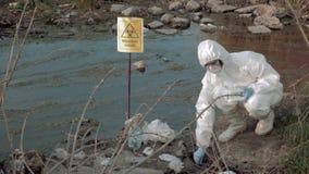 Zona de exclusión en la naturaleza, virólogo del hazmat en la ropa protectora que recoge la muestra infectada de agua en los tubo almacen de metraje de vídeo