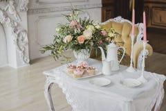 Zona de las decoraciones de la boda - tabla blanca con el ramo y las magdalenas Imagenes de archivo
