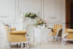 Zona de las decoraciones de la boda - tabla blanca con el ramo y las magdalenas Fotografía de archivo