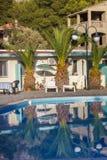 Zona de refrigeración del centro turístico con las palmeras de Phoenix y las camas del sol cerca de la piscina de agua azul Imagen de archivo