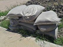 Zona de trabalho e construção, sacos da areia fina empilhados na grama imagem de stock