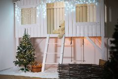 Zona decorada para o Natal A fachada de uma casa de madeira branca com escadas, balanços, árvore, decorada pelo ano novo fotografia de stock royalty free