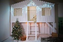 Zona decorada para o Natal A fachada de uma casa de madeira branca com escadas, balanços, árvore, decorada pelo ano novo foto de stock