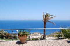 Zona di vista del Mar Egeo con la palma ed il POT dei fiori Fotografie Stock