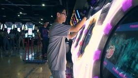Zona do jogo no shopping de MBK Homem asiático novo que joga Arcade Machine Drum Music Game e que empurra o controlador brilhante video estoque