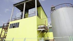 Zona industrial com encanamentos, a torre amarela da cabine com escadas e o reservatório enorme video estoque