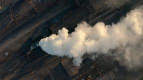 A zona industrial com um grande fumo branco grosso da tubulação vermelha e branca é derramada da tubulação da fábrica em contrast video estoque