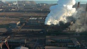 A zona industrial com um grande fumo branco grosso da tubulação vermelha e branca é derramada da tubulação da fábrica em contrast vídeos de arquivo