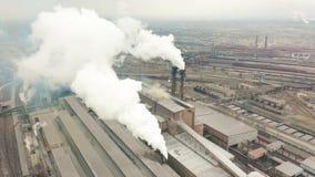 A zona industrial com um grande fumo branco grosso da tubulação vermelha e branca é derramada da tubulação da fábrica Poluição do filme
