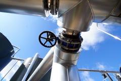 Zona industrial, tuberías de acero en el cielo azul Imagenes de archivo