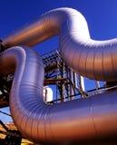 Zona industrial, tuberías de acero en la puesta del sol Imágenes de archivo libres de regalías