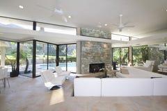 Zona para sentarse y chimenea de piedra en sala de estar espaciosa con la opinión de la piscina Imagen de archivo