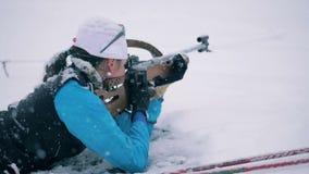 Zona que tira sitiada por la nieve con una leña femenina del biathlete almacen de video