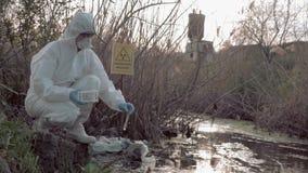 Zona radiactiva, químico de Hazmat en el traje protector que recoge la muestra infectada de agua para probar en el lago contamina metrajes