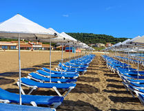 Zonbedden en paraplu's op een zandig strand Stock Foto
