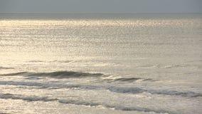 Zonbezinning in golven stock footage