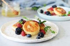 Zondagontbijt met kaastaart, honing, verse bessen en munt Kwarkpannekoeken of gestremde melkfritters verfraaide honing Royalty-vrije Stock Foto's
