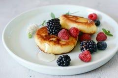 Zondagontbijt met kaastaart, honing, verse bessen en munt Kwarkpannekoeken of gestremde melkfritters verfraaide honing Stock Foto