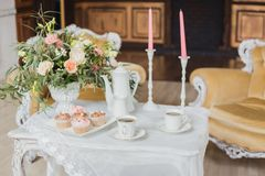 Zone de décorations de mariage - table blanche avec le bouquet et les petits gâteaux Images libres de droits