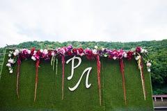 Zone de photo de mariage d'herbe artificielle, de fleurs et de grande lettre Images libres de droits