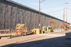 Zone de transit de matériaux de construction de routes près d'un mur en béton de soutènement et d'une route élevée Image stock