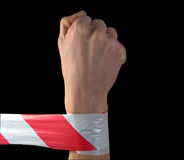 Zone under protection. Fist and protecting tape on a black background Stock Photo