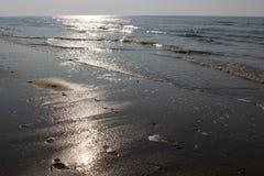Zonglans op de golven van de Noordzee bij zonsondergang Voetafdrukken in de natte zand en avondhemel Oostende, Belgi? royalty-vrije stock afbeeldingen