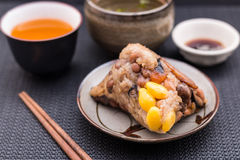 Zongzi or Asian Chinese sticky rice dumplings with Yellow tea, s. Oup, sauce and chopsticks on dark table surface. Zongzi is a traditional Chinese food eaten Royalty Free Stock Photos