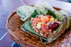 Zongzi, The glutinous rice wrapped in Lotus leaf put on the threshing basket stock photo