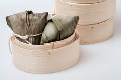 Zongzi in round bamboo crate. Asian Chinese glutinous rice dumpling or Zongzi, wrapped with reed leaves in round bamboo crate or round bamboo basket Stock Image