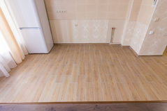 Zoning floor in interior, ceramic kitchen tiles bordered with laminate flooring in the living room Stock Photos