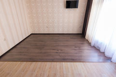 Zoning floor in interior, ceramic tile smoothly into the living room laminate Royalty Free Stock Photo