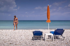 Zonlanterfanter en paraplu op leeg zandig strand Royalty-vrije Stock Afbeelding