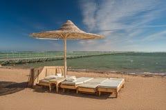 Zonlanterfanter onder de strandparaplu met mening bij de overzeese kust Blauwe hemel en de witte wolken over een toevluchtstrand Royalty-vrije Stock Foto's