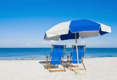 Zonlanterfanters en een strandparaplu op zilveren zand Stock Foto