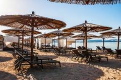 Zonlanterfanters en parasols op het zandige strand stock foto